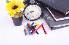 Rocznika zegar, sztuczna roślina, brogujący dzienniczki i kolorową kredkę na stole Obraz Royalty Free