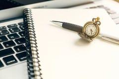 Rocznika zegarek na spirala otwartym notatniku i pióro na górze laptopu zdjęcia stock