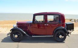 Rocznika zmrok - czerwony Austin Motorowy samochód parkujący na nadbrzeże deptaku Zdjęcie Stock