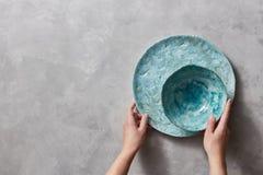 Roczniki malujący glazurujący talerzy naczynia na szarość betonu stole z bezpłatnej przestrzeni ror tekstem Dziewczyna chwyt hand zdjęcia stock