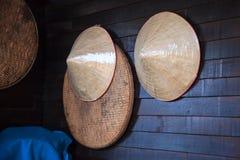 Roczniki wyplatający produktów bambusowi drewniani średniorolni kapelusze i omłotowy obwieszenie na nieociosanej drewnianej ścian zdjęcie royalty free
