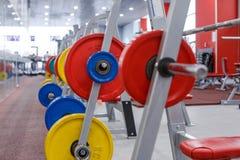 Rod con los pesos en el gimnasio Imágenes de archivo libres de regalías