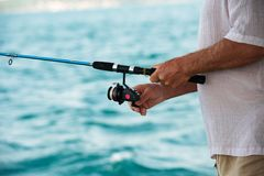 Rod in fisherman hands Royalty Free Stock Image