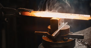 Rod hot iron on the anvil. Stock Images