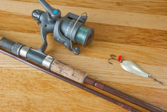 Rod with lure on wood desk Stock Photos