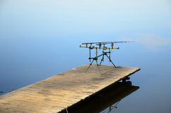 Rod pod with feeders with electronic bite alarms on pier. The one rod pod with two feeders with electronic bite alarms on a wooden pier by lake royalty free stock photos
