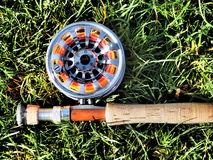 Rod and Reel. Shiny aluminium reel attached to fishing rod with cork handle on grass royalty free stock photo