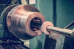 A roda abrasiva no mandrel na máquina na frente da parte cilíndrica está pronta para o metal que processa moendo fotografia de stock royalty free