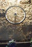Roda de bicicleta em uma parede de pedra do amarelo do tijolo na noite Israel, Dimona, ` da ANSR do `, 2018 Fotos de Stock Royalty Free