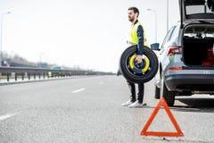 Roda de carro em mudança do homem na borda da estrada fotografia de stock royalty free