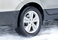 A roda de carro suja está na estrada do inverno imagem de stock