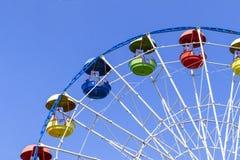 Roda de Ferris colorida grande colhida com céu azul atrás Fotos de Stock