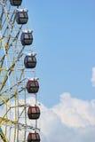 A roda de Ferris com as cabines no céu azul e no branco nubla-se o fundo Fotos de Stock