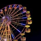 Roda de Ferris com as luzes que backlighting o céu noturno Imagem de Stock