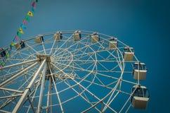 Roda de Ferris e bandeiras coloridas no parque de diversões contra o th fotografia de stock royalty free