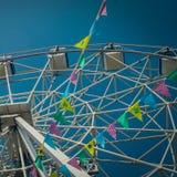 Roda de Ferris e bandeiras coloridas no parque de diversões contra o th imagens de stock royalty free