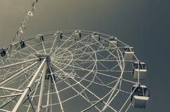 Roda de Ferris e bandeiras coloridas no parque de diversões contra o th foto de stock