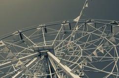 Roda de Ferris e bandeiras coloridas no parque de diversões contra o th fotos de stock royalty free