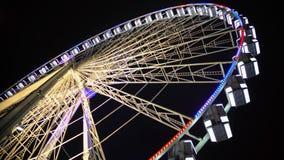 Roda de Ferris no parque de diversões, construção iluminada colorida que move-se lentamente filme
