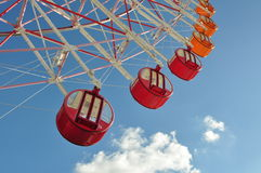Roda de ferris vermelha e alaranjada com c?u azul Imagens de Stock