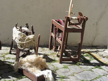 Roda de giro velha, fio de lãs cruas e lãs a cardar fotografia de stock