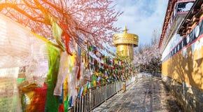 Roda de oração dourada grande com bandeiras da oração e o céu azul nebuloso b Imagens de Stock