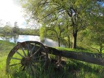 Roda de vagão de madeira por uma lagoa foto de stock