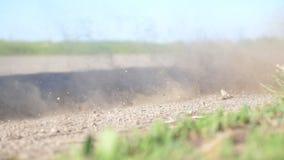 A roda do carro é deslizamento em uma estrada de terra durante o começo do movimento As pedras e a sujeira pequenas são voar para vídeos de arquivo