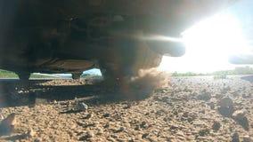 A roda do carro é deslizamento em uma estrada de terra durante o começo do movimento As pedras e a sujeira pequenas são voar para video estoque