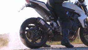 Roda do velomotor do esporte que começa girar no asfalto e que retrocede acima seixos e sujeira Motociclista que executa a neutra video estoque