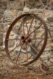 Roda oxidada do carro que descansa contra uma parede de pedra imagem de stock