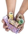 Rodado encima de billetes de banco euro sosténgase al lado de las manos femeninas Imagen de archivo libre de regalías