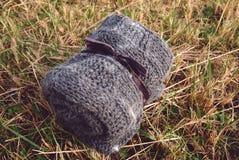 Rodado encima de gris hecho a mano hizo punto la manta de lana en la hierba secada Foto de archivo libre de regalías