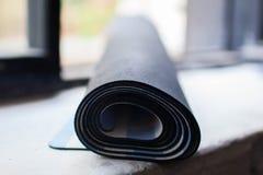 Rodado encima de la estera de la yoga Fotos de archivo