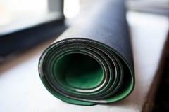 Rodado encima de la estera de la yoga Fotos de archivo libres de regalías