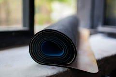 Rodado encima de la estera de la yoga Foto de archivo libre de regalías
