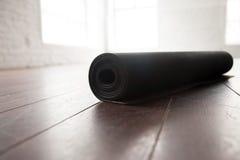 Rodado encima de la estera de la yoga en piso de madera natural Fotos de archivo