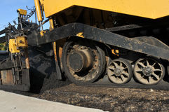 Rodas de uma máquina de pavimentação do asfalto na estrada nova fotografia de stock royalty free