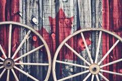 Rodas de vagão antigas com bandeira de Canadá Fotografia de Stock Royalty Free