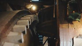 rodas denteadas de madeira enormes do moinho de vento 4K que giram lentamente O mecanismo holandês velho tradicional do moinho de filme