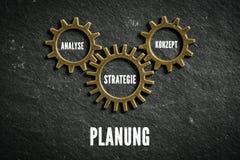Rodas denteadas que simbolizam a conexão dos componentes do ` do planeamento do ` no alemão imagem de stock