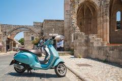 Rodas, Grecia 30 de mayo de 2018 Opinión de la calle Vespa parqueada delante de los restos de la iglesia de la Virgen del municip imagen de archivo
