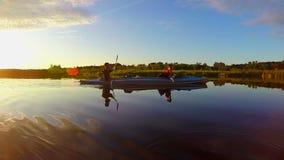 Rodd för två män på floden på solnedgången, turism, semester, långsam-mo stock video