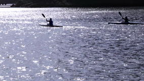 Roddare som utbildar på en solig dag i deras kanoter lager videofilmer