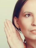 Roddelmeisje die met hand aan oor afluisteren royalty-vrije stock afbeelding