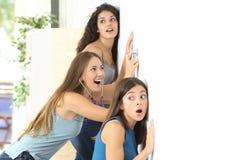 Roddelmeisjes die aan de buur luisteren Stock Foto