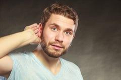 Roddelmens die met hand aan oor afluisteren stock foto