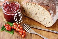Rode aalbesjam en vers brood Stock Foto's