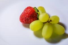 Rode aardbeien en witte druiven op witte achtergrond royalty-vrije stock afbeelding