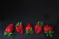 Rode aardbeien op een rij over zwarte Stock Fotografie